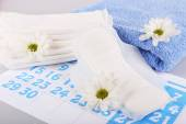 Sanitary pads, calendar, towel and white flowers — Stock Photo