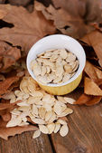 Pumpkin seeds in bowl on wooden background — Stock Photo