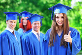 Graduate students wearing graduation hat and gown, outdoors — Foto Stock