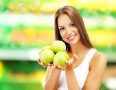 Shopping concept. Beautiful young woman with green apples on shop background — Stock Photo