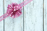 Wooden background with beautiful bow — Stock Photo