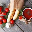 Homemade tomato juice in color mug, bread sticks, spices and fresh tomatoes on wooden background — Stock Photo #57577457