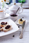 Fresh toasts with homemade butter and blackcurrant jam on wooden table, on bright background — Stock Photo