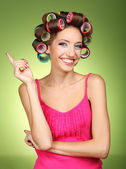 Beautiful girl in hair curlers on green background — Stockfoto