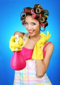 Beautiful girl in hair curlers on blue background — Stock Photo