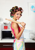 Beautiful girl in hair curlers in kitchen — Stock Photo