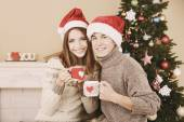 Nice love couple sitting with mugs in front of fireplace near Christmas tree. Woman and man celebrating Christmas — Stock Photo