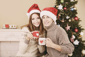 Nice love couple sitting with mugs in front of fireplace near Christmas tree. Woman and man celebrating Christmas — Stockfoto