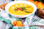 Pumpkin soup in plate and pumpkin slice — Stock Photo