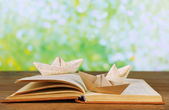 Origami boats on old book — Foto Stock