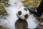 Soccer ball on ground in rainy day — Stock Photo
