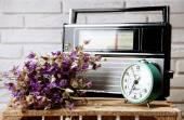 Retro radio, clock and flowers on table in room — Stock Photo