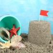Sandcastle with flag and plastic bucket on sandy beach on sea background — Stock Photo #57868377