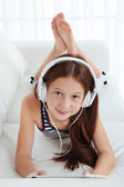 Beautiful little girl listening to music on sofa in room — Stock Photo