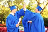 Graduate students wearing graduation hat and gown, outdoors — Stockfoto