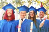 Graduate students wearing graduation hat and gown, outdoors — Stock Photo