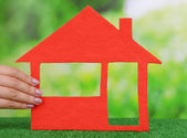 Woman hand holding paper house — Stock Photo