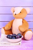 Toy bear and bowl of plums — Stock Photo
