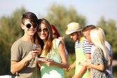 Young couple with friends on rest, outdoors — Stock Photo