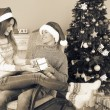 Young couple with gifts near Christmas tree — Stock Photo #59734625