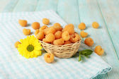 Yellow raspberries in basket and wildflower on checkered napkin on wooden background — Stock Photo