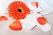 Sanitary pads, orange flower and rose petals — Stock Photo