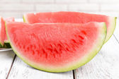Juicy watermelon on table on brick wall background — Stock Photo