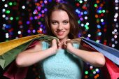 Beautiful young woman with shopping bags on bright lights background — Stock Photo