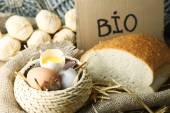 Eggs, bread and fresh milk in glass jug with inscription BIO  , on wooden background. Organic products concept — Stock Photo