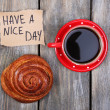 Composition of coffee, fresh bun and paper card on wooden background — Stock Photo #60780677