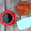 Composition of coffee, fresh bun and paper card on wooden background — Stock Photo #60780681