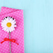 Camomile in metal spoon on pink polka dot napkin on wooden background — Stock Photo #60783203