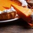 Composition of homemade pumpkin pie on plate and fresh pumpkins on wooden background — Stock Photo #60786225