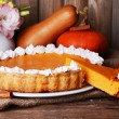 Composition of homemade pumpkin pie on plate and fresh pumpkins on wooden background — Stock Photo #60786229