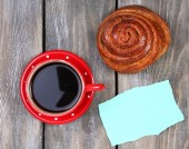 Composition of coffee, fresh bun and paper card on wooden background — Stock Photo