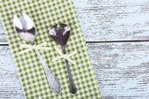 Metal spoons on green checkered napkin on wooden background — Stock Photo