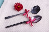Metal spoons and dark red flower on napkin on fabric background — Stock Photo