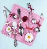 Metal spoons on pink polka dot napkin on wooden background — Stock Photo
