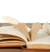Origami airplanes on old book, on wooden table, on white background — Stock Photo