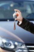 Businessman holding car key outdoors — Stock Photo