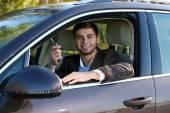 Man with car key in car — Stock Photo