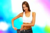 Beautiful young woman with big jeans on bright background — Stock Photo