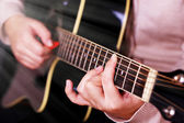 Acoustic guitar in female hands — Stock Photo