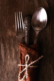Old tableware wrapped in paper on sackcloth napkin on wooden background — Stock Photo