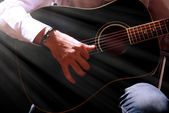 Young musician playing acoustic guitar, on dark background — Stock Photo
