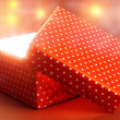Gift box with bright light on red background — Stock Photo #60834047