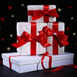 Beautiful gifts with red ribbons, on dark background — Stock Photo #60839551