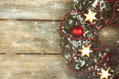 Green Christmas wreath with decorations on wooden background — Stock Photo