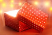 Gift box with bright light on red background — Stock Photo