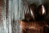 Old tableware wrapped in sackcloth napkin on wooden background — Stock fotografie